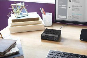 Close up image of a Dell WYSE Desktop (Model 3040) on a desk in a home office with Dell 23-inch S2340L monitor and KM714 wireless keyboard (Tangerine). Micro Desktop is shown on next to a small stack of books.