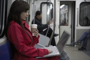 Woman Sitting On Train Typing On Laptop --- Image by © Blue Jean Images/Corbis, polycom