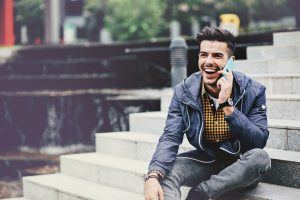 Smiling man, sitting outdoors at urban environment talking on the phone, with copy space.